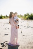 Fotografie beautiful young mother with adorable toddler on beach