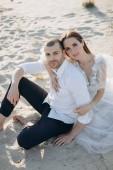 Fotografie mladý nádherný pár objímání a sedí na písečné pláži