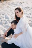 krásný usměvavý pár sedí na písečné pláži