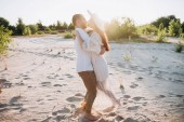 beautiful young couple hugging on sandy beach with back light