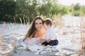 Photo young happy mother spending time with adorable son on beach