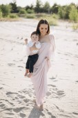 Fotografie attractive mother holding little son on beach