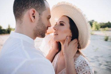 tender man hugging beautiful young woman in hat