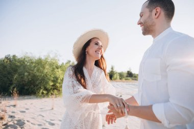 beautiful young smiling couple holding hands on beach