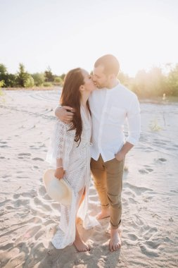 happy couple hugging and kissing on beach with backlit