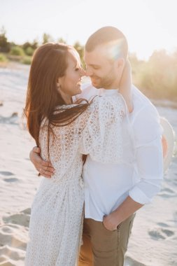 beautiful smiling couple embracing on beach with sunlight