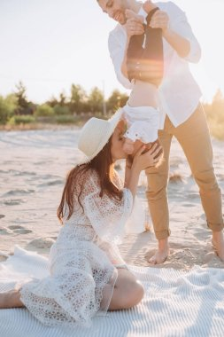 beautiful mother kissing her little son on beach