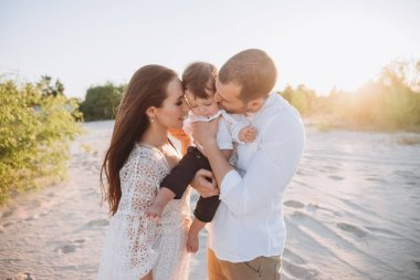 happy parents hugging and kissing adorable son on beach