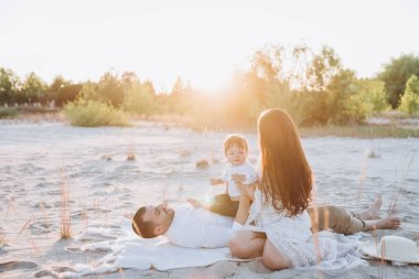 happy family spending time with son on beach with sunlight