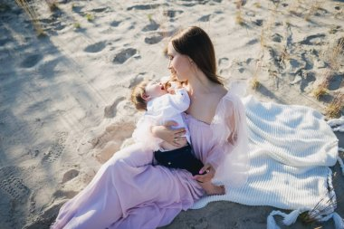 young mother sitting with little son on beach