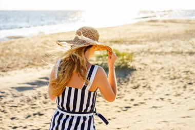 back view of woman in straw hat walking on sandy beach