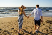 rear view of affectionate couple holding hands and walking on sandy beach on summer day