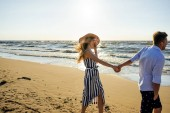 Fotografie side view of young smiling couple in love holding hands on sandy beach in Riga, Latvia
