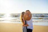 částečný pohled pár v lásce schovává za slaměný klobouk na písečné pláži v Rize, Lotyšsko