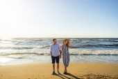 Fotografie young couple in love holding hands on sandy beach in Riga, Latvia