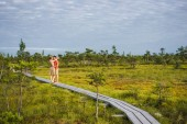 Fotografie couple in love hugging on wooden bridge with blue sky and green plants on background