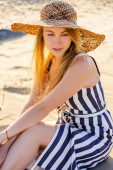 Photo portrait of attractive young woman in straw hat resting on sandy beach