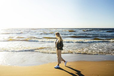 side view of young woman in stylish clothing walking on seashore on summer day