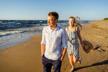 portrait of happy couple in love walking on sandy beach in Riga, Latvia