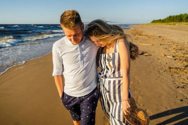 portrait of young couple in love walking on sandy beach in Riga, Latvia