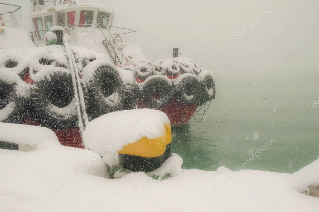 Snow covered tugboat at foggy and snowy seaport