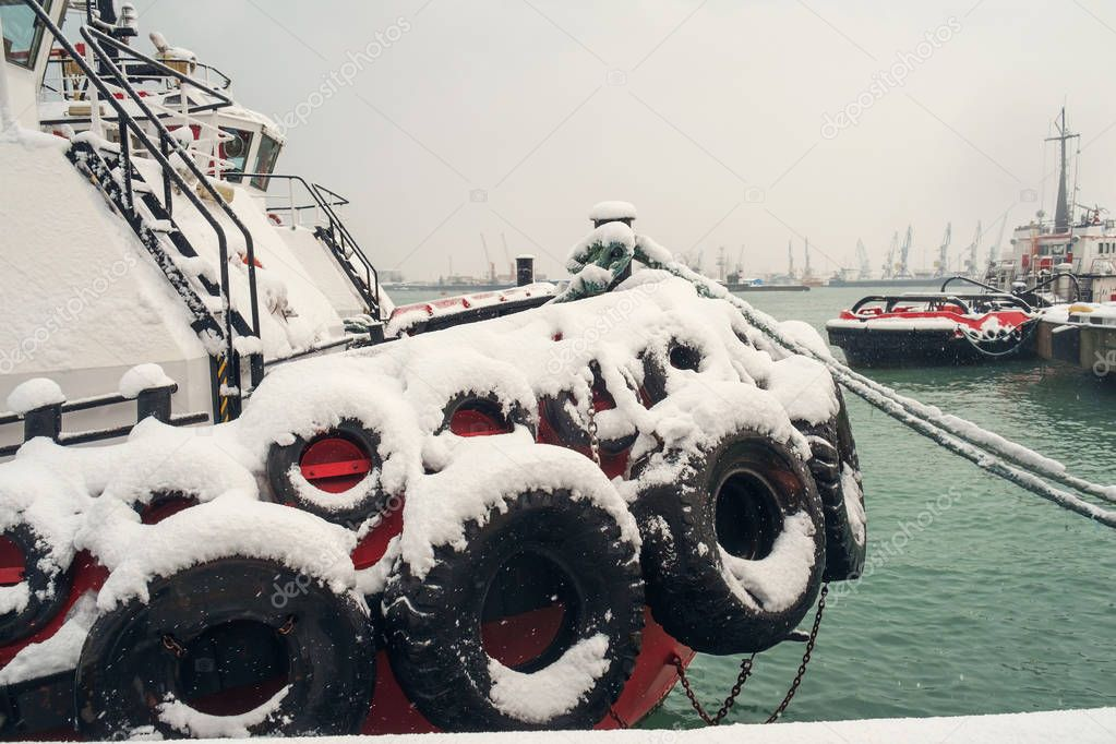 Snow covered tugboat at snowy seaport