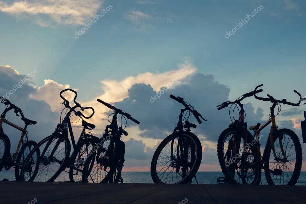 The silhouette of bikes, row of bikes on the beach wit blue cloudy sky background