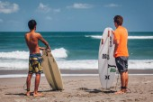 rear view of two young men standing with surfboards on sandy beach