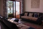 Kényelmes szoba kanapéval és tengerre néző erkély. Cozy belső lakás. A nappaliban stílusos dekoráció és bútorzat található. Kanapék, párnák és szőnyeg a padlón. Ocean Villa szoba. Vakáció és relaxáció koncepció.