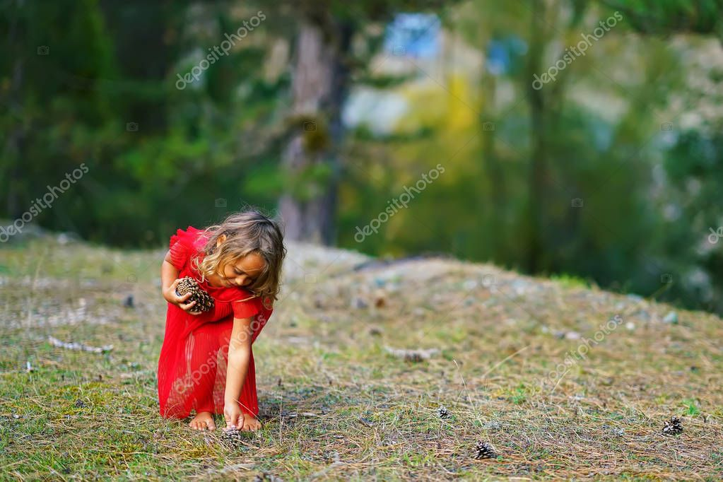Little girl in a red dress collects cones in the forest in Greece