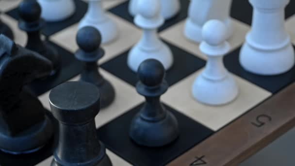 Motion shot of chess pieces are standing on wooden board at table indoors irrl.