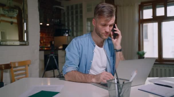 handsome male freelancer talking on the phone with smile at home with laptop computer Spbas