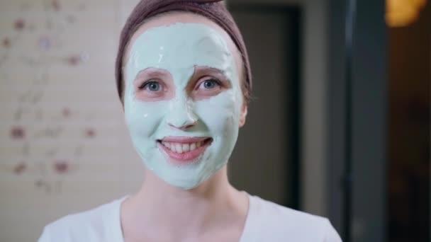 Mladá žena s maskou na obličeji pózuje pro kameru v domácím interiéru spbas.