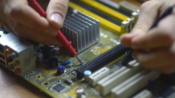 Die Elektronik repariert Mikrochips und Leiterplatten auf der Hauptplatine. Service Nahaufnahme. Elektroniker Irrl