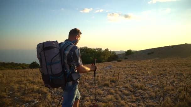 man hiker walk on mountain hike travel peak with black sea bakground. Spbd tourist climb in crimea during sunset