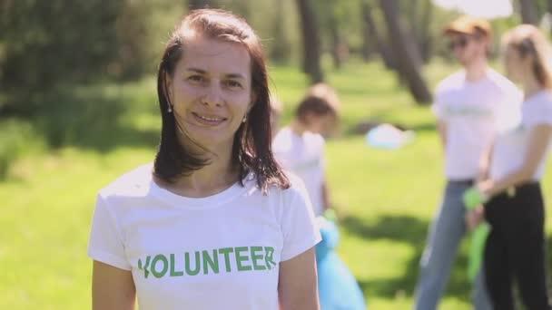 Porträt einer Freiwilligen, die an einem Sommertag für die Kamera posiert und im grünen Park lächelt.