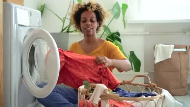 Az afro-amerikai nő szennyest tett a mosógépbe otthon, Spbd. a nők végzik a házimunkát