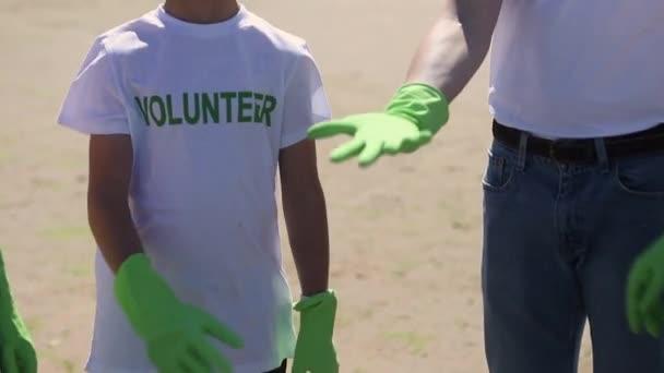 Hände unkenntlich gemachter Freiwilliger haben Spbi zusammengestellt. Familie mit Kindern im T-Shirt. Müll reinigen