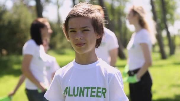 Porträt eines freiwilligen Jungen, der an einem Sommertag beim Putzen im grünen Park für die Kamera posiert.