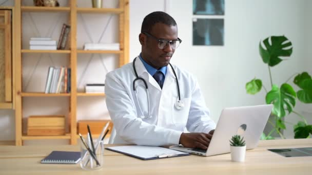 African American male doctor is working with laptop and writing at table in clinic spbas.