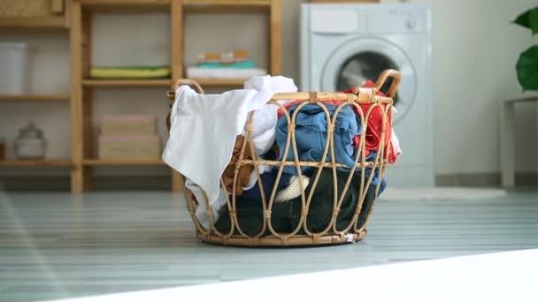 vorbereiteter Korb mit schmutziger Freizeitkleidung auf dem Fußboden des Badezimmers mit Waschmaschine. Spbd Inland