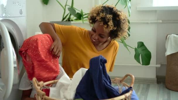 Amerikanische Afroamerikanerin und kleines Mädchen haben Spaß, während sie auf dem Fußboden in der Waschküche sitzen.