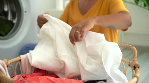 Amerikai nő ruhák mosógép, ül a padlón a mosókonyhában otthon spbd.