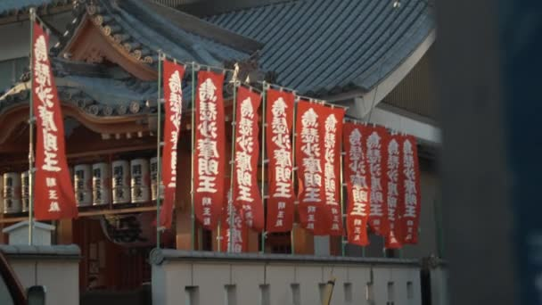 Red flags with inscriptions waving against Japanese temple