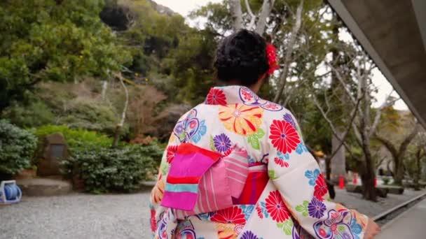 Žena v chůzi v japonské zahradě v Kamakura krásné kimono