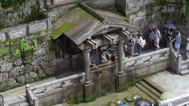 People washing hands outside kiyomizu temple