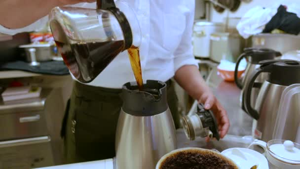 Coffee being poured into jugs by woman