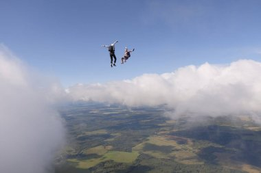 SKydiving. Two skydivers are flying above white clouds.
