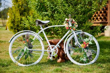 White bicycle decorated with flowers in bloom in rural