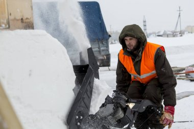 Worker removes snow in a blizzard using a snowplow